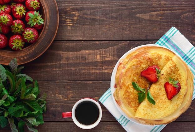 딸기와 딸기 잼, 민트 장식 무늬와 황금 팬케이크의 더미. 상위 뷰