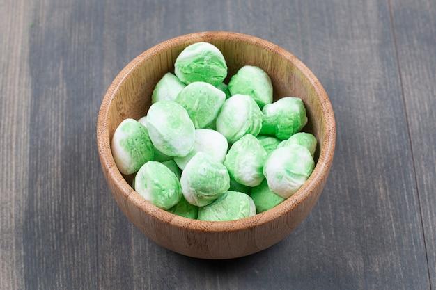 나무 그릇에 녹색 사탕 더미