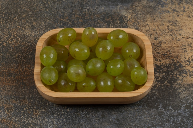 Куча зеленого винограда на деревянной миске.