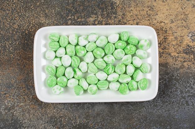 하얀 접시에 녹색 멘톨 사탕 더미입니다.
