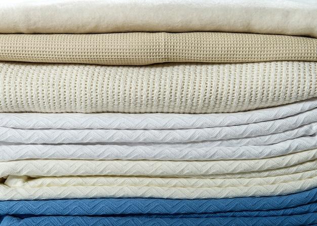 Куча хлопчатобумажных салфеток льняных вафель ручной работы, полотенца на белой льняной предпосылке. разные цвета. реквизит для фото еды. натуральная вафельная льняная хлопчатобумажная ткань.