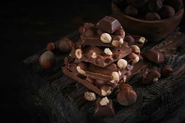 헤이즐넛 밀크 초콜릿과 견과류 어두운 나무 테이블에 더미