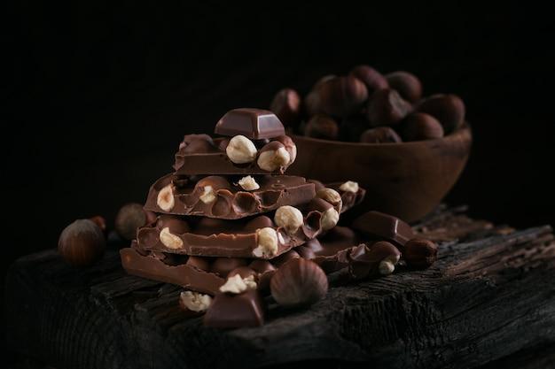 헤이즐넛 밀크 초콜릿과 견과류 어두운 나무 벽에 더미