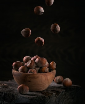 暗い木製の背景に木製のボウルにヘーゼルナッツヘーゼルナッツの山。殻の中のフライングナッツ。