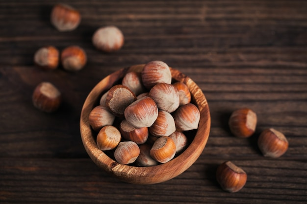 暗い木製の背景に木製のボウルにヘーゼルナッツヘーゼルナッツの山。彼らの殻の新鮮なナッツ。