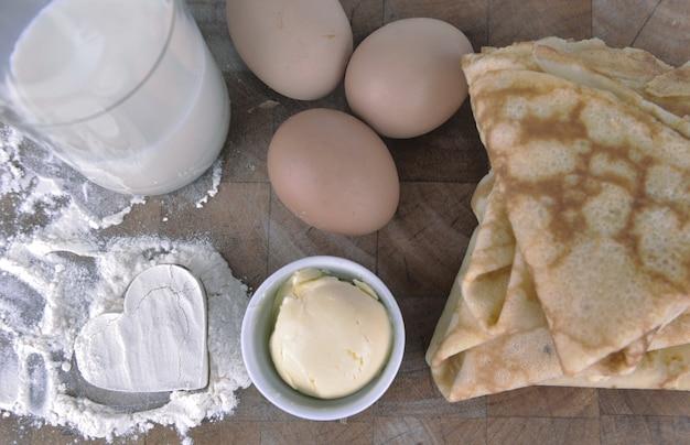 Куча домашних французских блинов с сердцем в муке, яйца и сливочное масло на доске