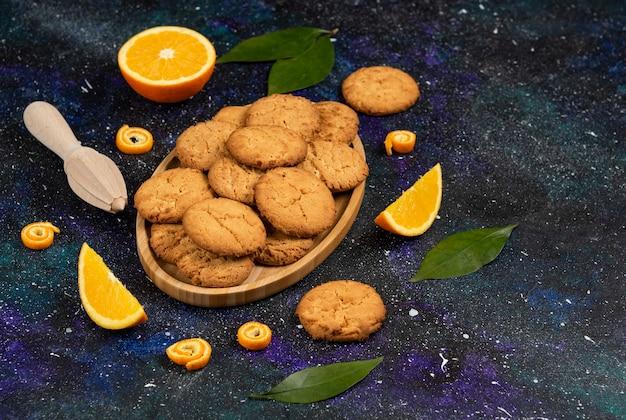 집에서 만든 신선한 쿠키 더미와 어두운 테이블 위에 반으로 자르거나 얇게 썬 오렌지.