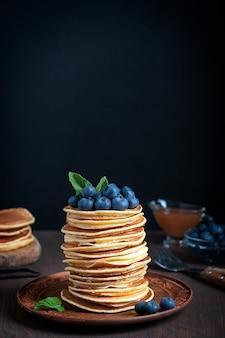 Куча домашних блинов, украшенных черникой и мятой, подается на тарелке на столе