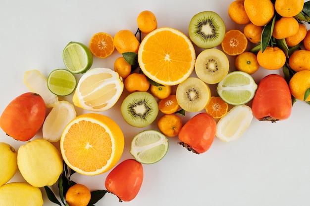 키위, 오렌지, 라임, 레몬과 같은 즙이 많은 녹색 및 주황색 익은 과일 더미