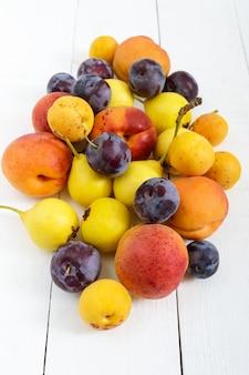 Куча сочных летних фруктов на белом деревянном столе