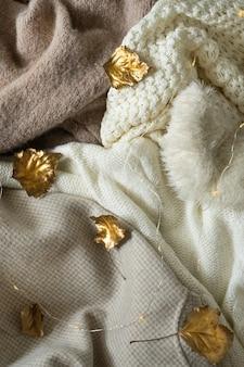 Куча вязаной одежды с осенними золотыми листьями теплый фон трикотаж пространство для текста осень зима ...