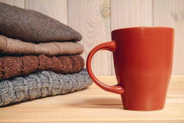 ニットのセーターの山と木製の背景にカップ