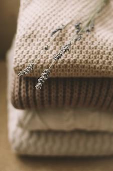 Куча вязаных свитеров с цветком лаванды