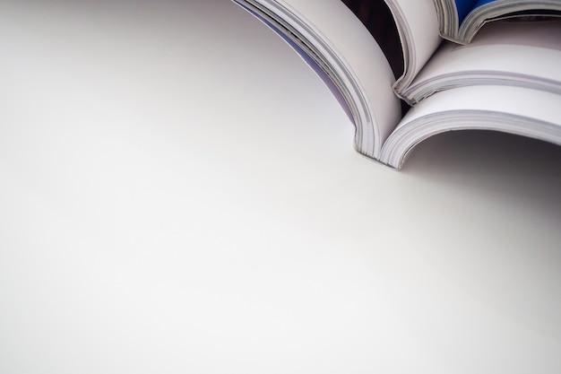 거실에있는 흰색 테이블에 잡지 스택 더미를 닫습니다.