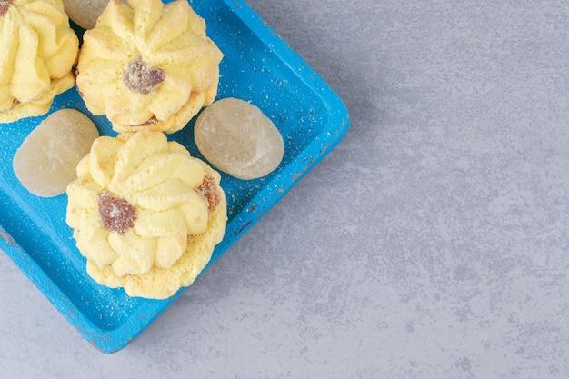 Куча мармеладов и печенья на синем подносе на мраморе