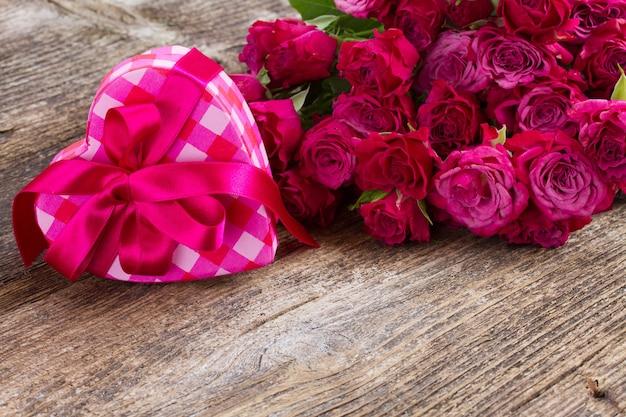 Куча розовато-лиловых маленьких свежих роз и сердечная коробка на деревянном фоне