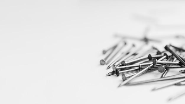 白いテーブルの上の金属の釘の山