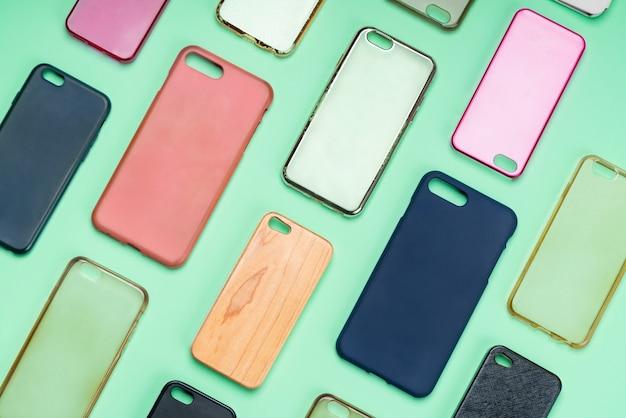 携帯電話用の色とりどりのプラスチック製裏表紙の山。緑の背景にスマートフォンプロテクターアクセサリーの選択。シリコン製の電話の背もたれやスキンが隣り合っている