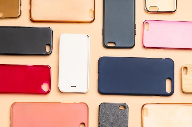 携帯電話用の色とりどりのプラスチック製裏表紙の山。ニュートラルな背景のスマートフォンプロテクターアクセサリーの選択。シリコン製の電話の背もたれやスキンが隣り合っている