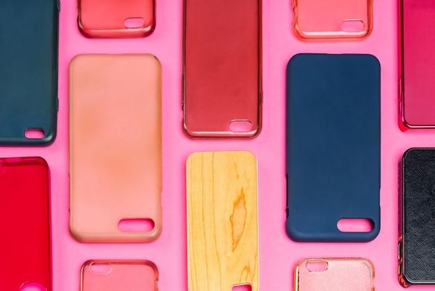 携帯電話用の色とりどりのプラスチック製裏表紙の山。ピンクの背景にスマートフォンプロテクターアクセサリーの選択。シリコン製の電話の背もたれやスキンが隣り合っている
