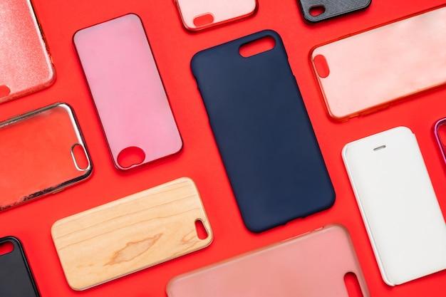 携帯電話用の色とりどりのプラスチック製裏表紙の山。赤い背景のスマートフォンプロテクターアクセサリーの選択。シリコン製の電話の背もたれやスキンが隣り合っている