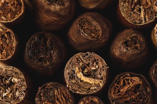 Куча новых кубинских сигар заделывают на деревянном столе
