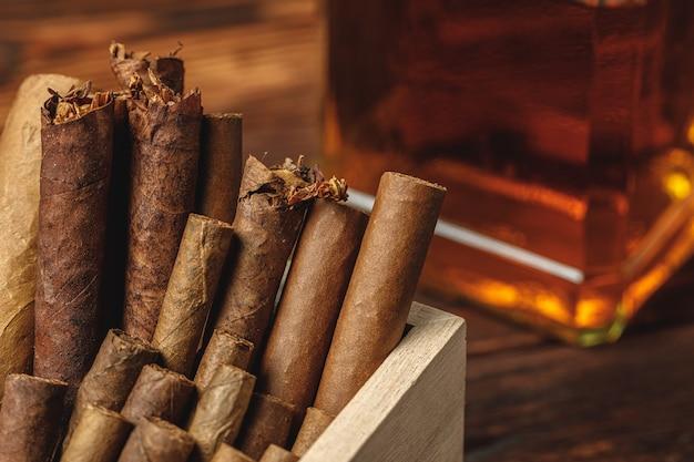 Куча новых кубинских сигар возле бутылки алкоголя