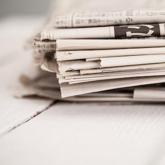 Куча газет на белом столе
