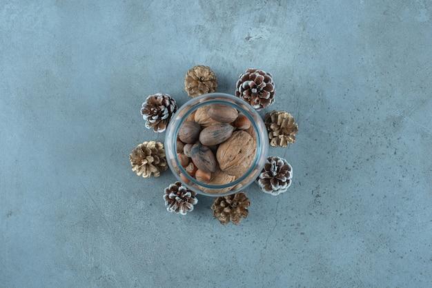 대리석 표면에 소나무 콘 가운데 유리 항아리에 견과류 더미