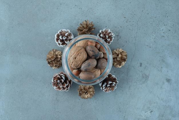 Куча орехов в стеклянной банке среди сосновых шишек на мраморной поверхности