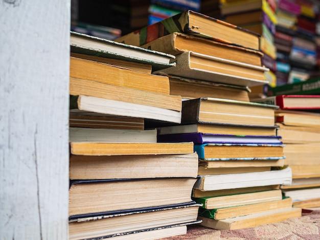 古い本の山。黄ばんだページの汚れた本。カウンター上の本のスタック