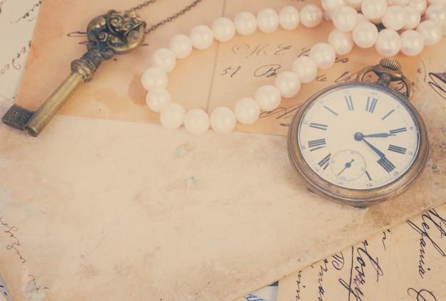오래된 편지 더미와 복사 공간이 있는 골동품 시계 빈티지 bckground, 복고풍 톤