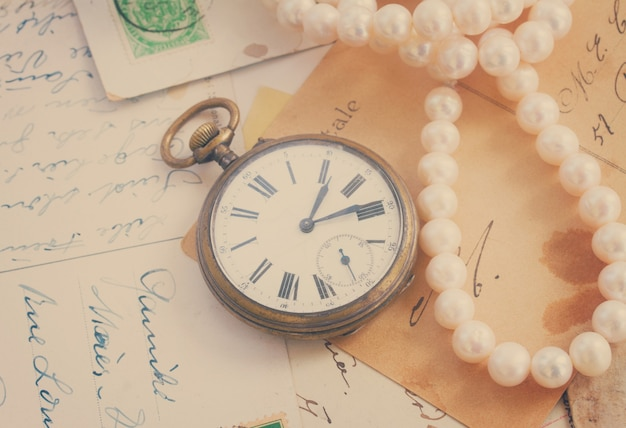 골동품 시계와 진주가 있는 오래된 편지 더미, 복고풍 톤