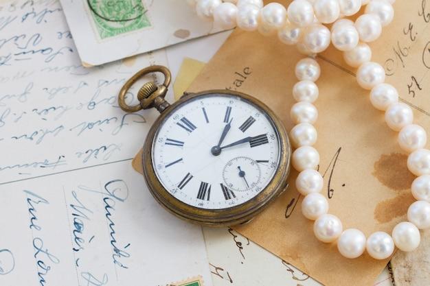 골동품 시계와 진주가 있는 오래된 편지 더미