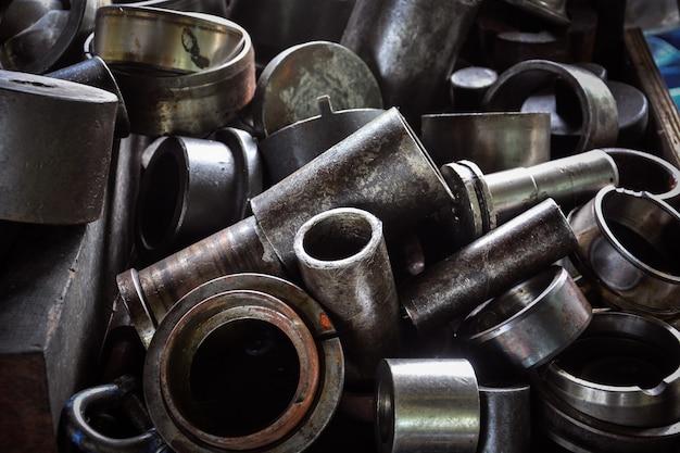 Куча старых металлических деталей машин на заводе
