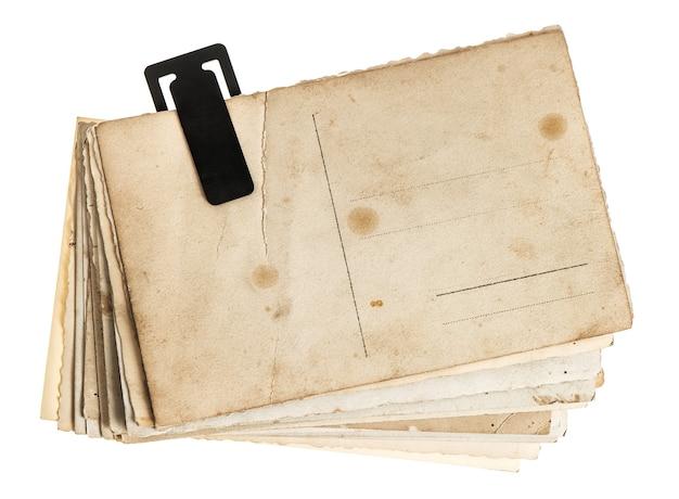 흰색 배경에 고립 된 오래 된 엽서의 더미입니다. 클립이 있는 빈티지 종이 시트. 복고풍 디자인