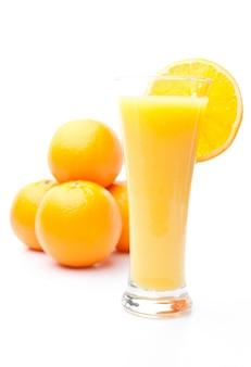 オレンジジュースのガラスの後ろにオレンジの山