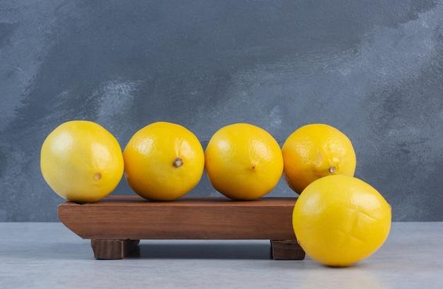 나무 보드에 유기농 레몬 더미입니다.