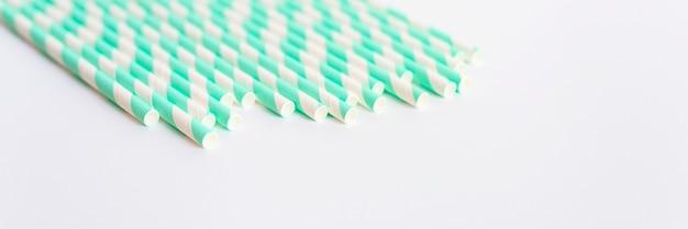 白い背景の上のパーティーのための紙の縞模様の白と緑のストローの山。テキスト用のスペース