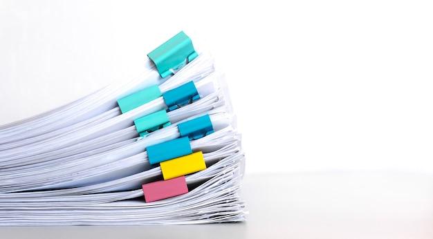 Куча бумаги с красочными зажимами. стек документов, размещенных на рабочем столе в деловом офисе.