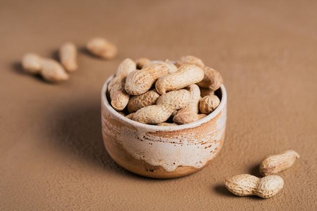 茶色の背景のボウルにピーナッツの山。彼らの殻の新鮮なナッツ。