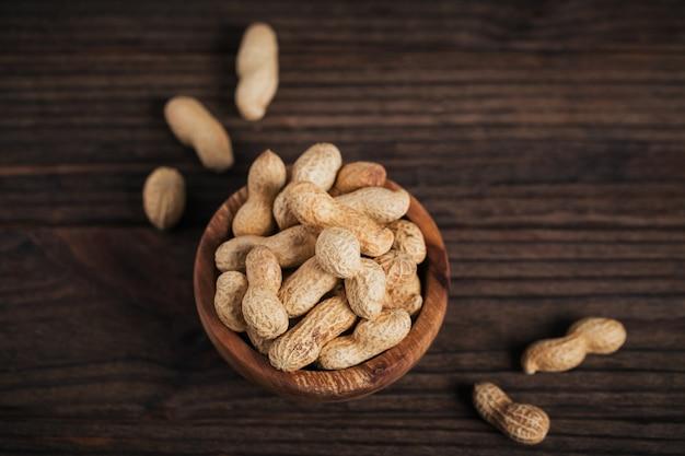 暗い木製の背景のボウルにピーナッツの山。彼らの殻の新鮮なナッツ。