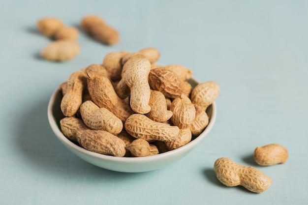 水色の表面のボウルにピーナッツの山。彼らの殻の新鮮なナッツ。