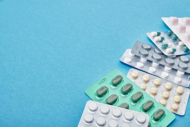 Куча таблеток в блистерных упаковках на синем фоне с копией пространства сверху