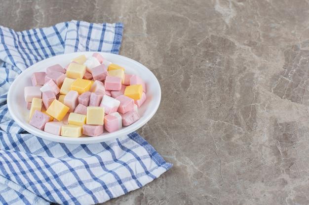 회색 배경 위에 하얀 접시에 분홍색과 흰색 사탕 더미.