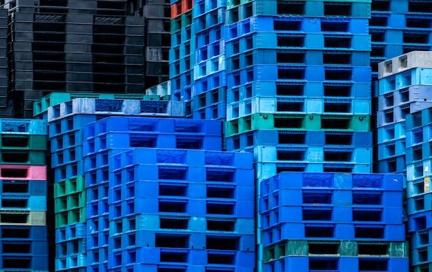 プラスチック製の輸送用パレットの山。工場の倉庫に積み上げられた工業用プラスチックパレット。