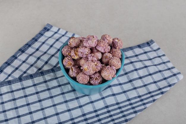 대리석 표면에 수건에 봉사 크기 그릇에 팝콘 사탕의 더미.