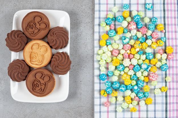大理石の背景にクッキーの大皿の横にあるタオルの上にポップコーンキャンディーの山。高品質の写真