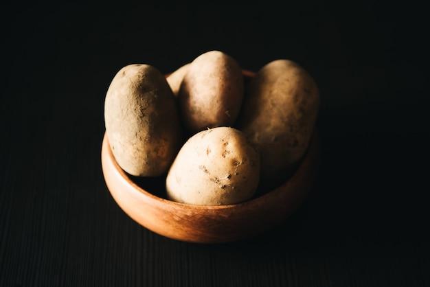 Куча картофеля в деревянной тарелке на черном.
