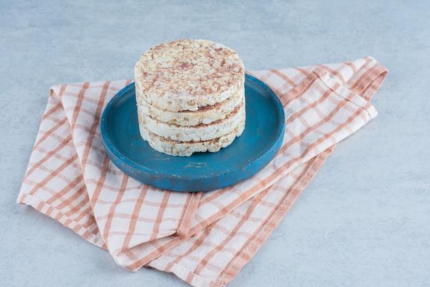 Куча воздушных рисовых лепешек на деревянной тарелке на полотенце на мраморе.